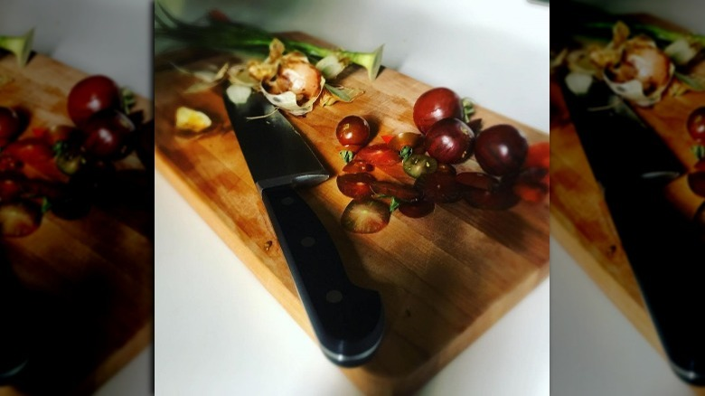 cutting board with vegetables and a knife