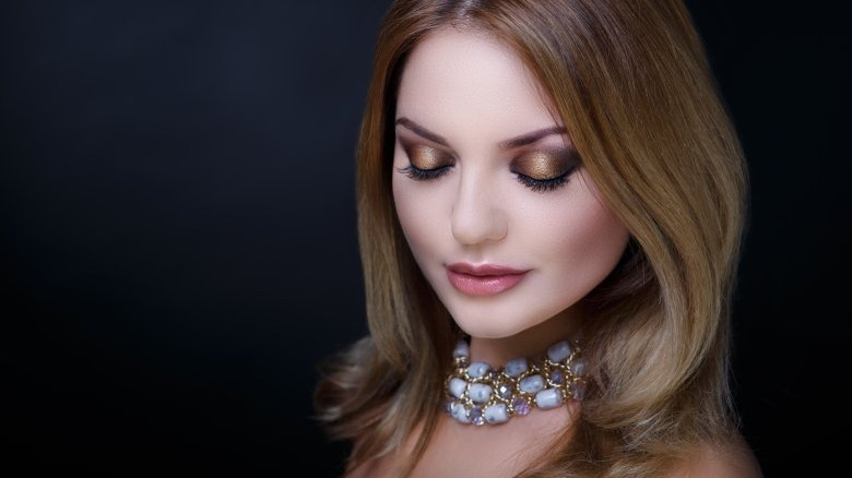 trendy woman with large necklace and bold eyeshadow
