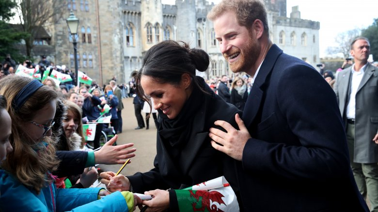 Meghan Markle and Prince Harry signing autographs