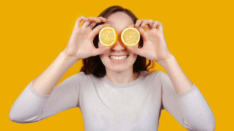 woman holding lemon halves in front of eyes