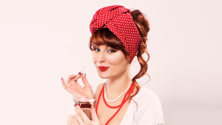 A redheaded woman smelling perfume