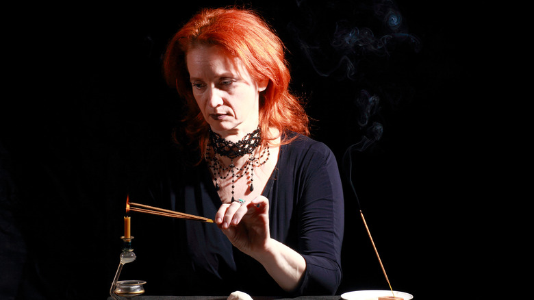 A redheaded woman lighting incense