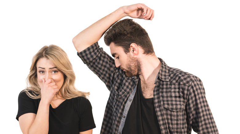woman holing her nose as man smells his underarms