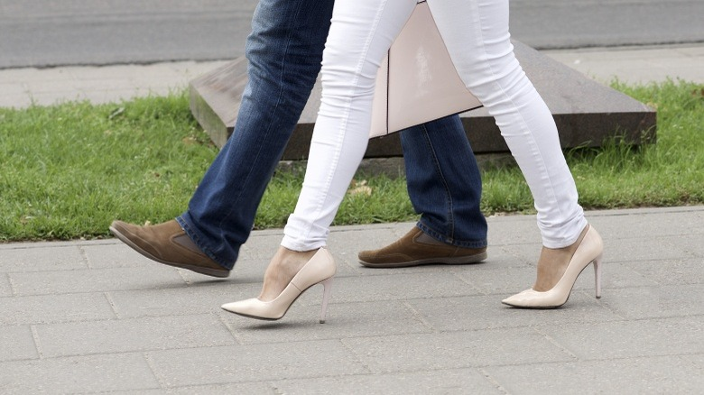 98647acea399 woman high heels man walking couple