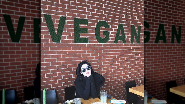 "Kat Von D in front of a ""vegan"" sign"