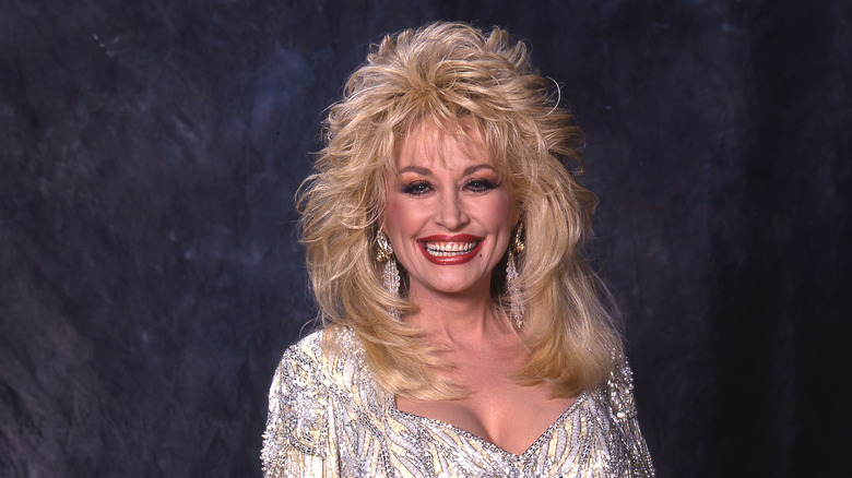 Dolly Parton smiling, wearing a silver dress