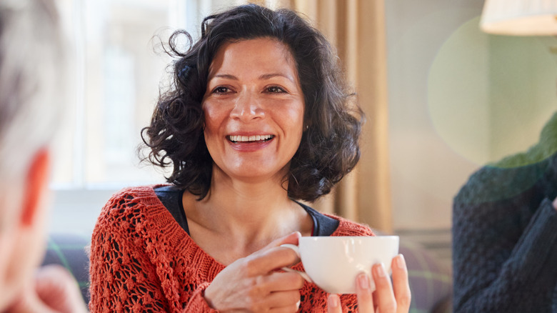middle-aged woman smiling holding teacup