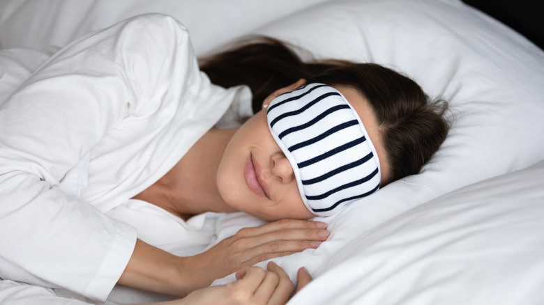 A woman asleep in bed with an eye mask