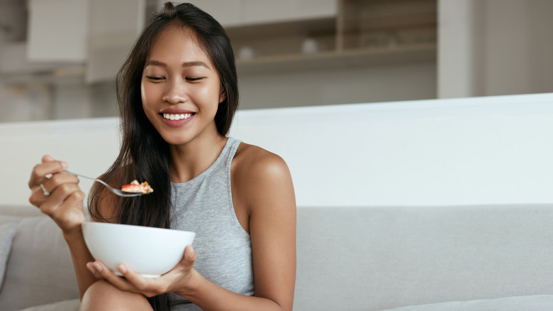 woman smiling while eating oatmeal