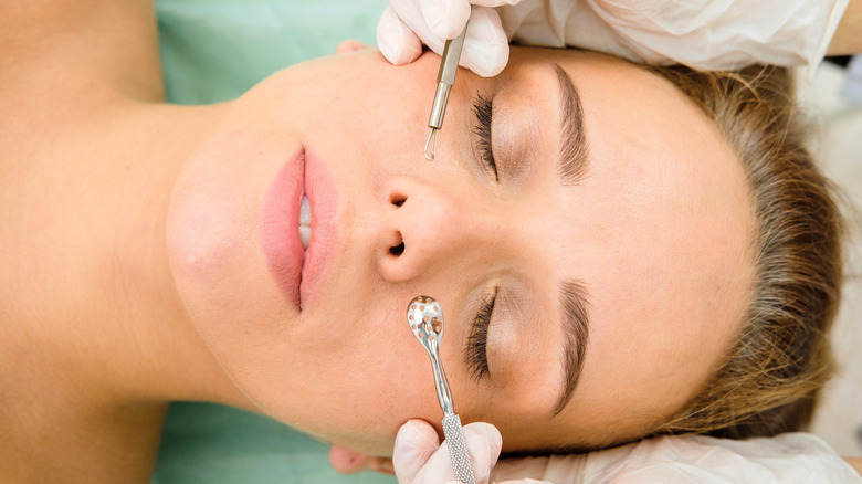 woman with acne getting blackhead extractions