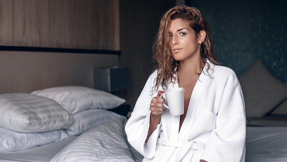 a woman holding a mug of water in bed
