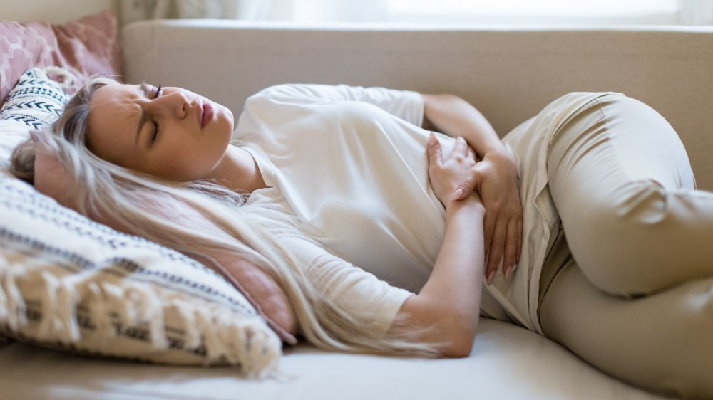 a woman on the couch holding her stomach in pain